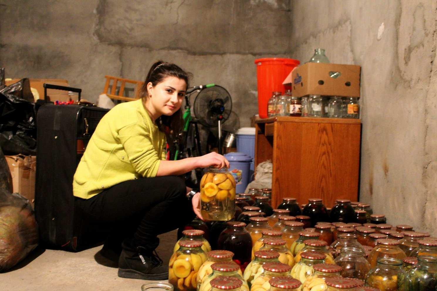 15-летняя Офелия Хачатрян демонстрирует запасы консервов, заготовленные жителями дома.