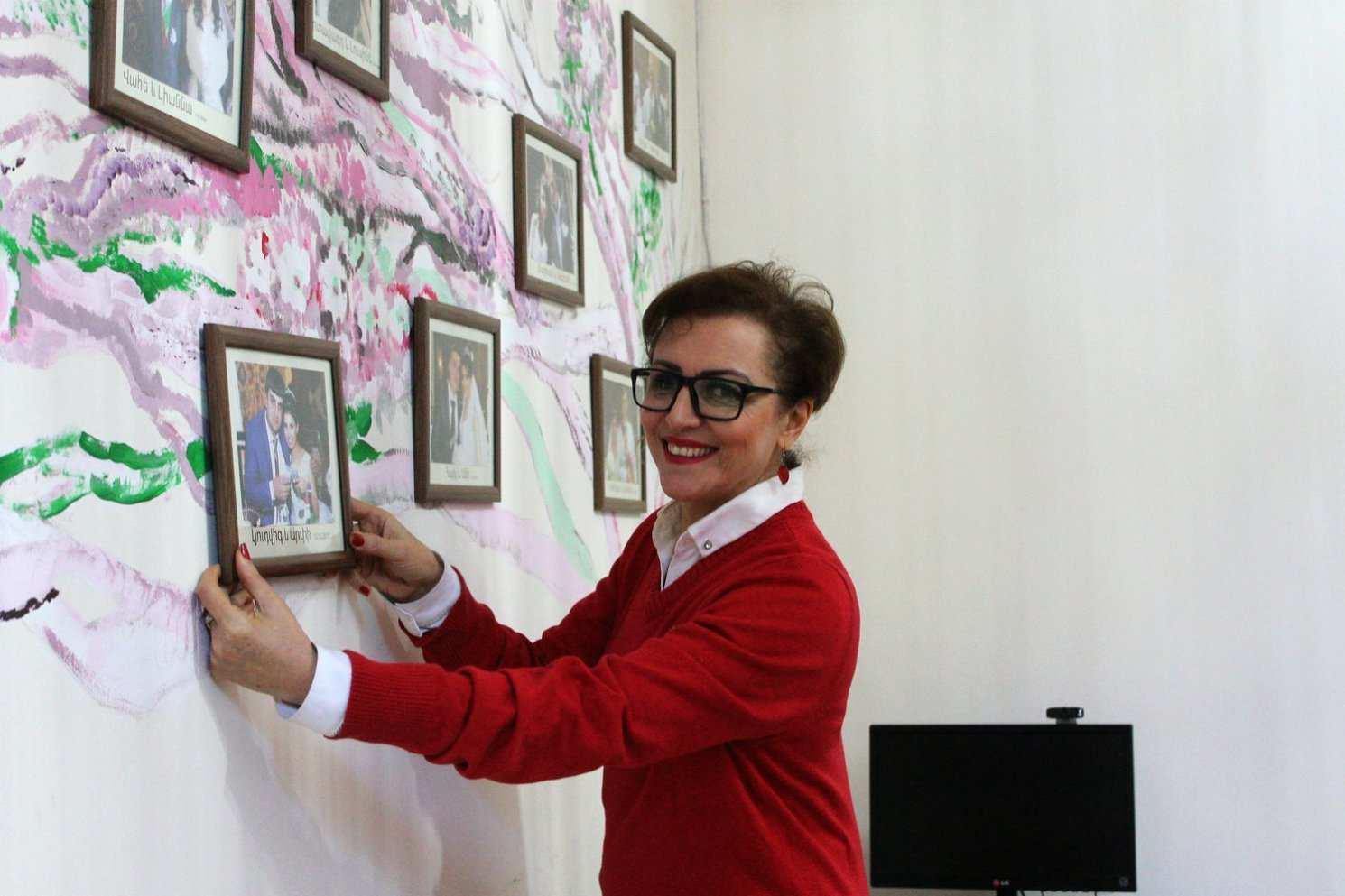 """Директор организации """"Наш Дом"""" Тигрануи Карапетян показывает стену, на которой висят свадебные фотографии ее бывших воспитанниц."""