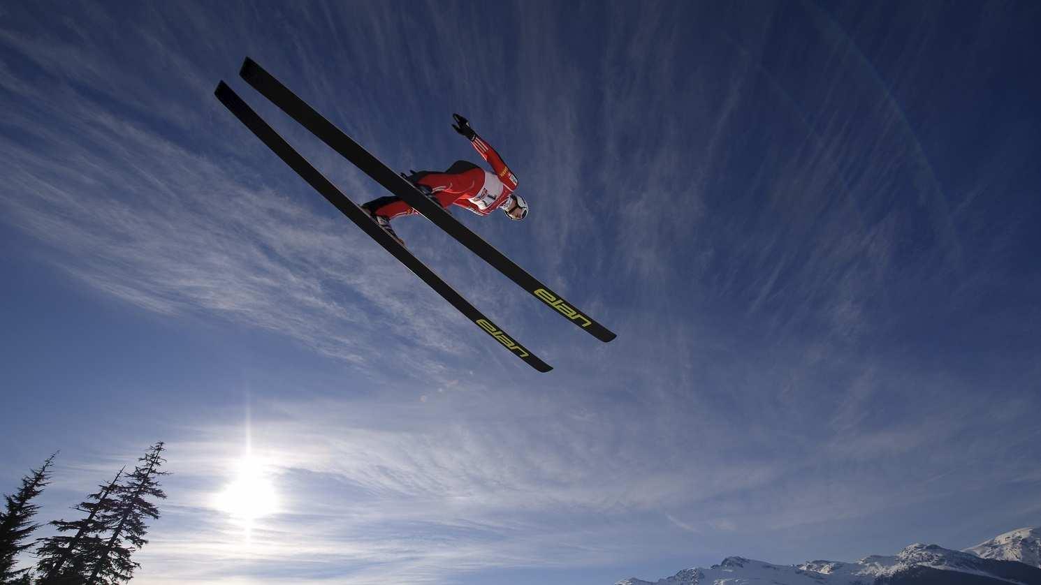 Skier-ski-jump-fly-sky-sun-mountains-4k-3840x2160